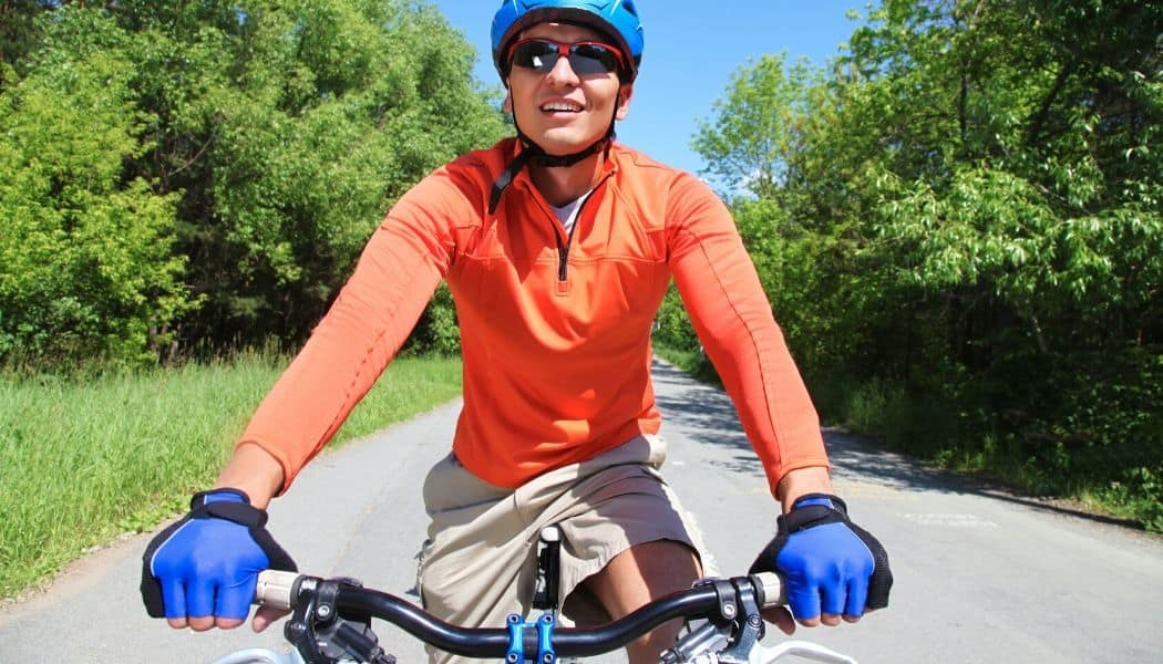man cycling wearing blues gloves for hand numbness