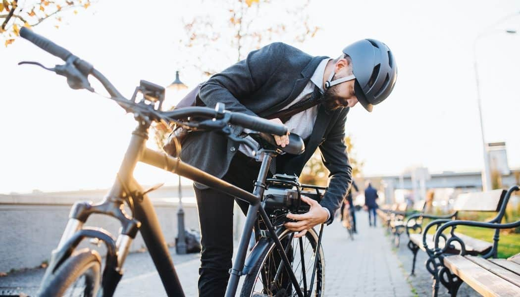 business man fixing electric bike in city
