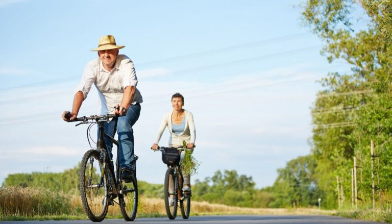 couple riding bikes for seniors with trees background