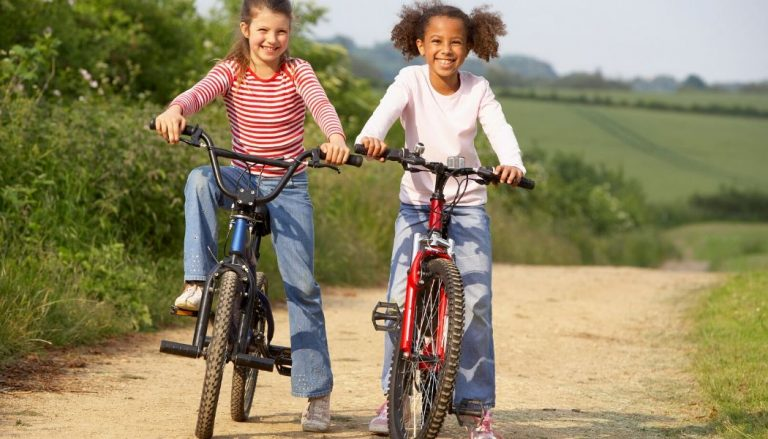 kids riding 20 inch bikes with road background