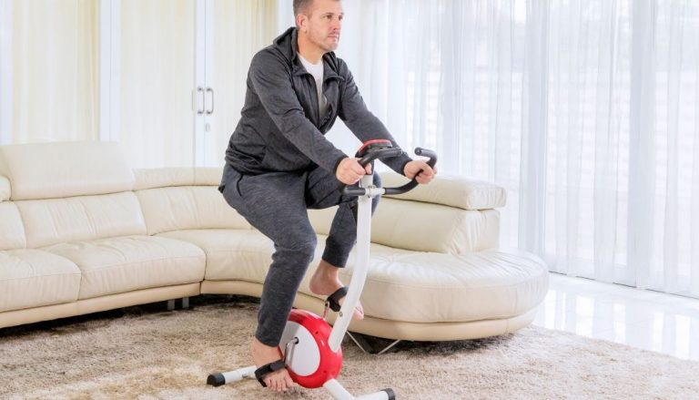 man using a folding exercise bike at home